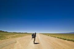 Reiziger met rugzak op een eenzame weg in woestijn stock afbeelding