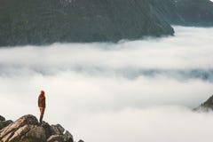 Reiziger op klip boven de stijging van de wolkenreis in bergen stock fotografie