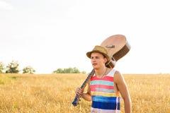Reiziger, romantische reisachtergrond die, jonge mens huis, kerel met gitaar verlaten die bij zonsonderganggebied lopen Royalty-vrije Stock Fotografie