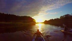 Reizigers die bij zonsondergang, adembenemende mening, sport, langzaam-mo kayaking stock videobeelden