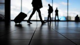 Reizigers die in luchthaven aan vertrek door roltrap voor venster, silhouet lopen stock foto's