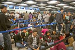 Reizigers die in luchthaven bij sneeuwstorm wachten Stock Afbeeldingen