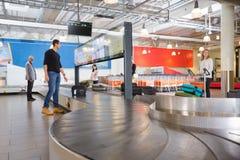 Reizigers die op Bagage van Transportband bij Luchthaven wachten royalty-vrije stock foto