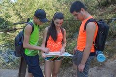 Reizigers, wandelaars die op vakantie een kaart lezen Twee jonge Toeristen met Rugzakkenreis Drie jonge Toeristen met Rugzakkenre royalty-vrije stock foto's