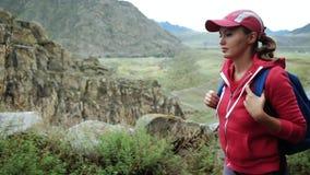 Reizigersmeisje die in GLB met rugzak stenenbergen beklimmen De mening van de close-up Achtergrondbergen en rivier stock videobeelden