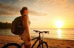 Reizigersmeisje die met rugzak van mening van mooie zonsondergang genieten Royalty-vrije Stock Afbeeldingen