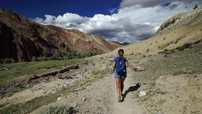 Reizigersmeisje die op een klippenweg lopen op een steenberg Er zijn mooie berg en bewolkte hemel op de achtergrond stock video