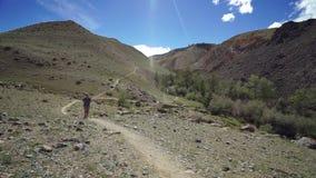 Reizigersmeisje die op een klippenweg lopen op een steenberg Er zijn mooie berg en duidelijke hemel op de achtergrond stock videobeelden