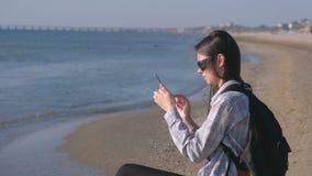 Reizigersmeisje met een rugzak blogger op een zandig overzees strand en het maken van foto en video op mobiele telefoon stock footage