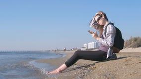 Reizigersmeisje met een rugzakzitting op een zandig overzees strand en het typen van een bericht op mobiele telefoon stock footage