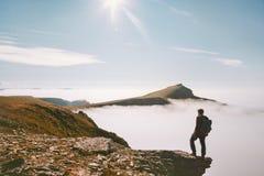 Reizigersmens die alleen in bergen over wolken wandelen royalty-vrije stock afbeelding