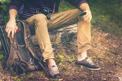 Reizigersmens het ontspannen in bos met fotocamera, rugzak en thermosflessen het drinken thee stock afbeeldingen