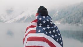 Reizigersmens met vlag die van Amerika zich in de snow-covered bergen dichtbij mooi meer bevinden Wandelaar die bekijken stock videobeelden