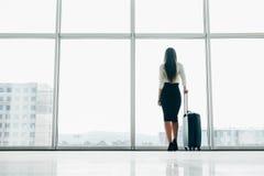 Reizigersonderneemster die op vertraagde vlucht bij luchthavenzitkamer wachten die zich met bagage het letten op tarmac bij lucht royalty-vrije stock foto's