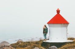 Reizigersvrouw die dichtbij vuurtoren van mistige overzeese mening geniet die solo reist stock foto's