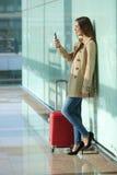 Reizigersvrouw gebruikend een slimme telefoon en wachtend in een luchthaven Stock Afbeelding