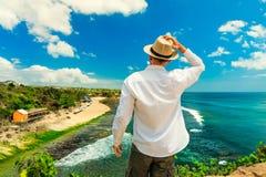 Reizigerswandelaar bovenop bergklip op tropisch strand als achtergrond Bali, Indonesië royalty-vrije stock foto