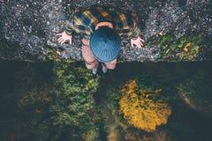 Reizigerszitting op de rand van de klippenbrug met bos luchtmening Royalty-vrije Stock Foto's