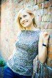 Reizvolle blonde Dame, die nahe einer Backsteinmauer steht Lizenzfreies Stockbild