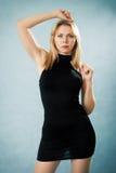 Reizvolle blonde Dame im schwarzen Kleid Stockfotos