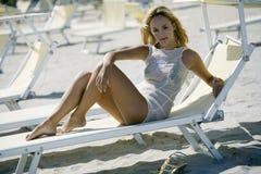 Reizvolle blonde Frau auf einem Klappstuhl am Strand Stockbilder