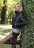 Reizvolle blonde Frau in der Natur nahe einem Baum Lizenzfreie Stockfotografie