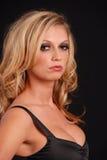 Reizvolle blonde Frau in der schwarzen Oberseite Stockfotografie