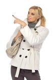 Reizvolle blonde Frau, die auf copyspace zeigt Lizenzfreie Stockfotos