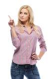 Reizvolle blonde Frau, die auf copyspace zeigt Lizenzfreie Stockfotografie