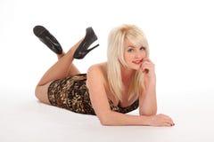 Reizvolle blonde Frau, die auf Fußboden mit einem Lächeln liegt Lizenzfreie Stockbilder