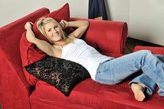 Reizvolle blonde Frau, die auf roter Couch sich entspannt Stockfotos