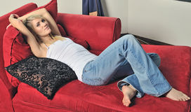 Reizvolle blonde Frau, die auf roter Couch sich entspannt Lizenzfreie Stockfotografie