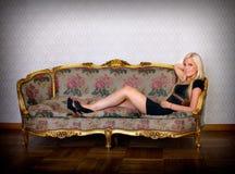 Reizvolle blonde Frau, die auf Sofa sich hinlegt Stockfotografie