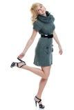 Reizvolle blonde Frau, die eine graue Knitkleidholding trägt Lizenzfreies Stockfoto