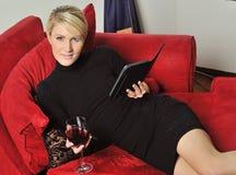 Reizvolle blonde Frau, die einen Eleser mit Wein liest Stockbilder