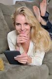 Reizvolle blonde Frau, die Tablette Computer/Eleser verwendet Lizenzfreie Stockfotografie
