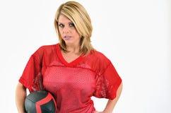 Reizvolle blonde Frau im roten Ineinander greifenfußball Jersey Stockfotografie