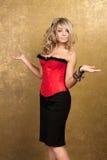 Reizvolle blonde Frau im roten Korsett und im Rock Stockbilder