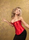 Reizvolle blonde Frau im roten Korsett und im Rock Lizenzfreie Stockbilder