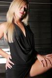 Reizvolle blonde Frau im schwarzen Minikleid Stockfoto