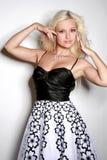 Reizvolle blonde Frau im Schwarzweiss-Kleid Stockbilder