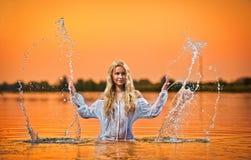 Reizvolle blonde Frau im Wasser am Sonnenuntergang Lizenzfreie Stockfotos