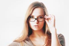 Reizvolle blonde Frau mit den Gläsern getrennt Lizenzfreie Stockfotografie