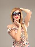 Reizvolle blonde Frau mit der Sonnenbrilleaufstellung Lizenzfreies Stockfoto