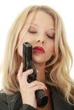 Reizvolle blonde Frau mit Pistole Stockfoto