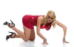 Reizvolle blonde Frau, welche die rote Sequinkleidaufstellung trägt Lizenzfreie Stockfotografie