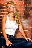 Reizvolle Blondine gegen Backsteinmauer Stockfotografie