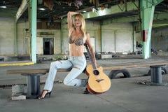 Reizvolle Blondine mit einer Gitarre (1) Stockbild