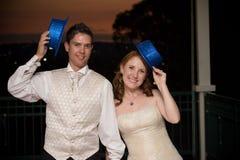 Reizvolle Braut und junger stattlicher Bräutigam mit blauen Hüten Lizenzfreies Stockfoto