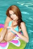 Reizvolle Brunette-Frau, die auf Pool-Spielzeug schwimmt Stockbild